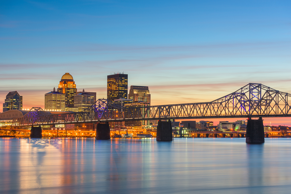 The skyline of downtown Louisville with several tall buildings stands against a blue sky with a bridge in the foreground.