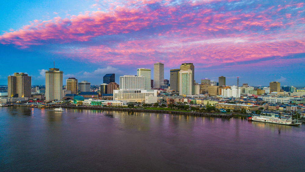 Cityscape on the shore of a wide river. A steamboat floats near the shoreline under pink clouds in a blue sky