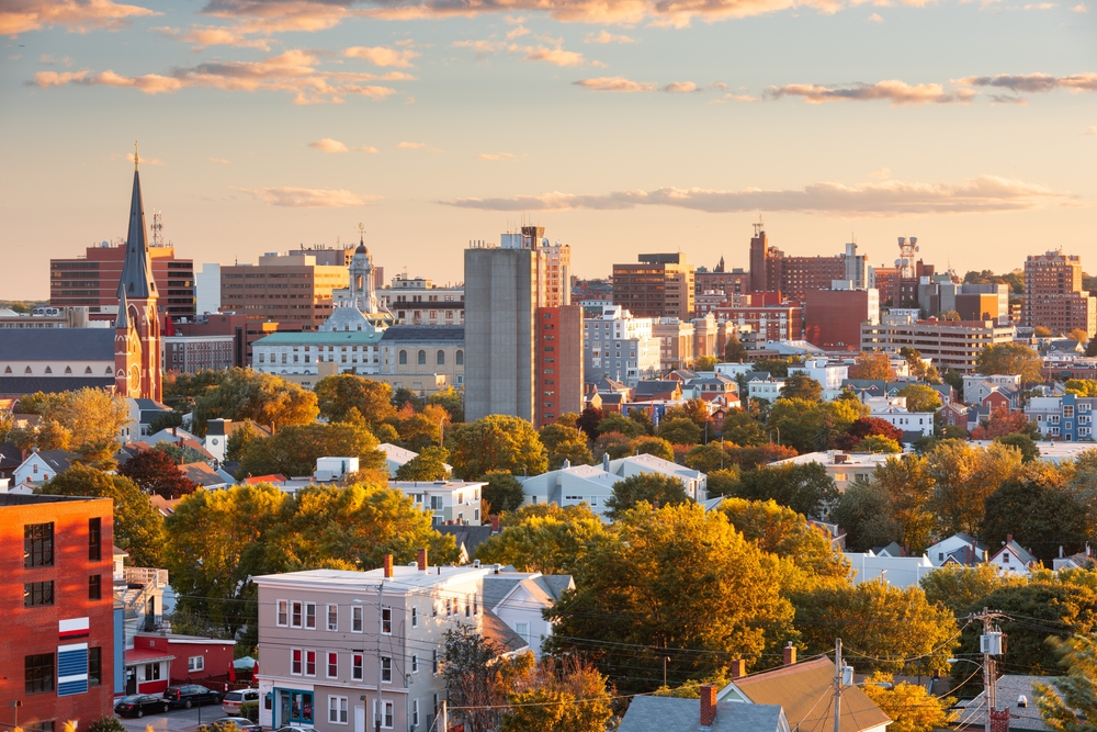 A city with homes, tall brick buildings, and green trees sits under a partly cloudy orange and blue sky at dusk.