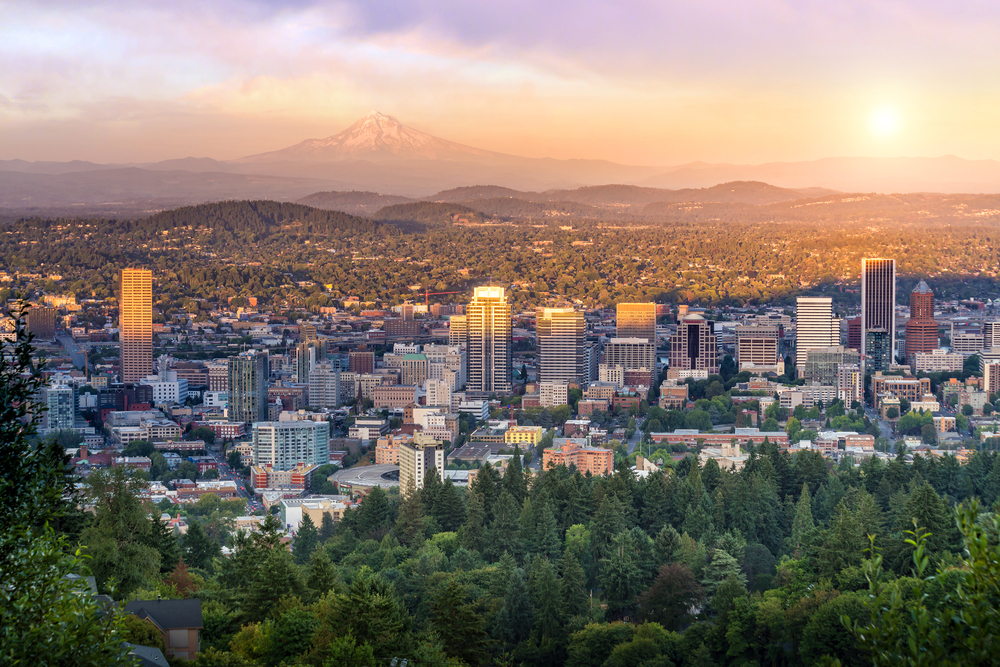 The downtown Portland skyline at dusk is dominated by the looming Mt. Hood in the background under a pale purple and golden sky.