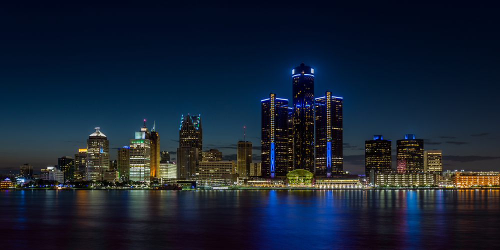 Bright lights shine in the buildings of a metropolitan skyline at night, reflected in a calm, black body of water.