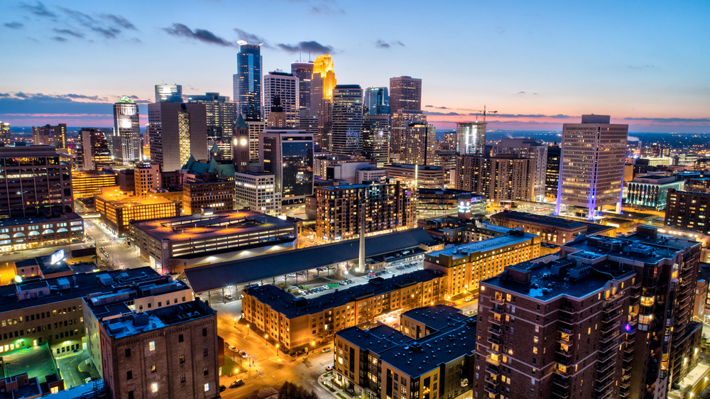 A downtown skyline glows with lights illuminating its tall buildings at dusk.