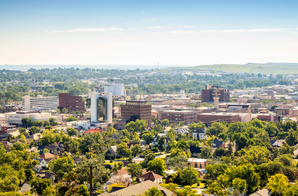 A city with buildings surrounded by green trees under a pale blue sky.