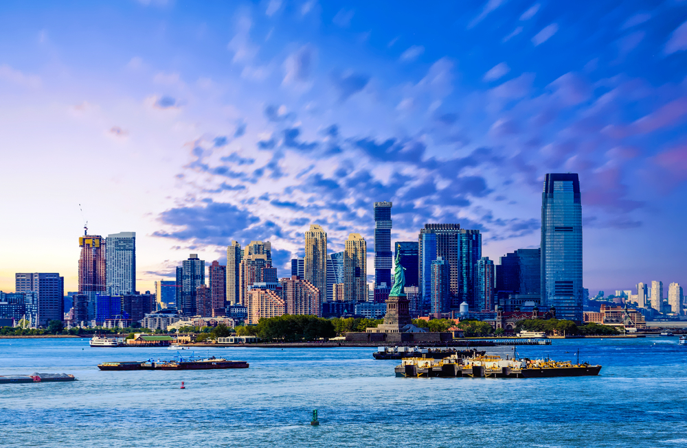 A city skyline under purple and blue sky. Boats float in the Harbor around the Statue of Liberty.