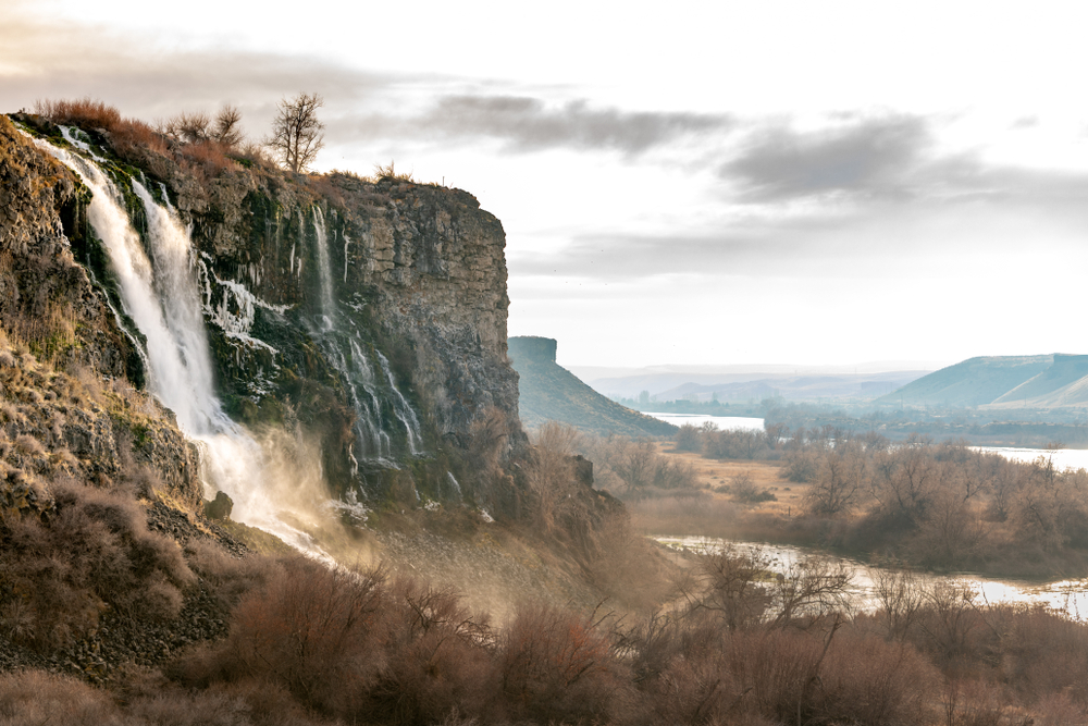 Beautiful waterfall with warm colored mist and Snake River