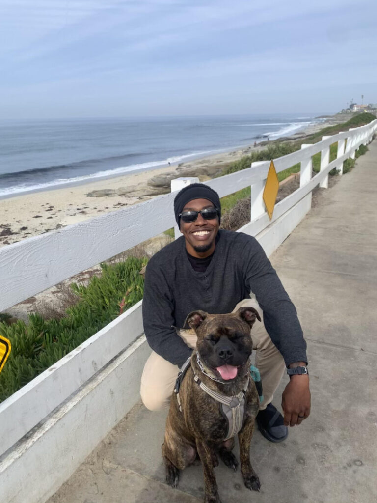 Man poses with his dog near the beach