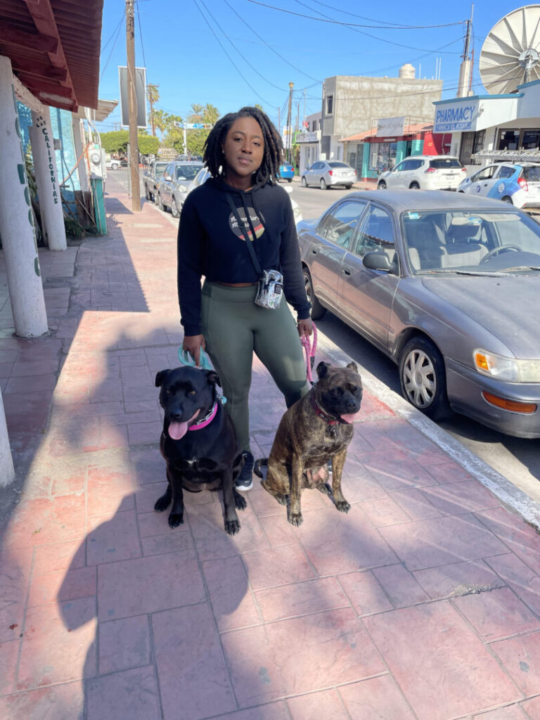 Woman poses with her two dogs on the sidewalk