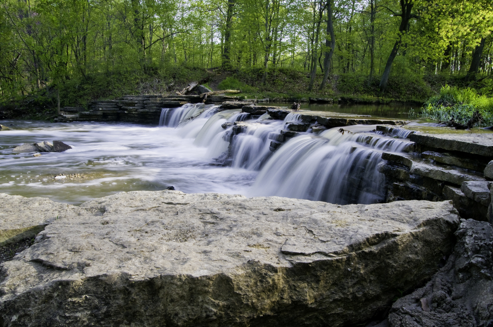 Sawmill Creek spills over a beautiful waterfall on a spring day at Waterfall Glen Forest Preserve in DuPage County, Illinois.