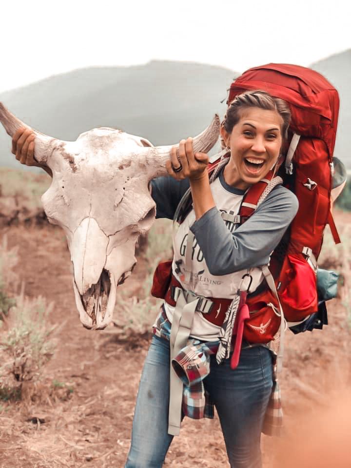 Woman holds up animal skull