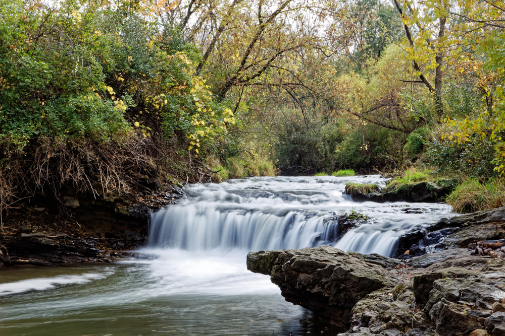 The water flows over the lower waterfall in Briggs Woods Park. The waterfall is surrounded by fall colors.