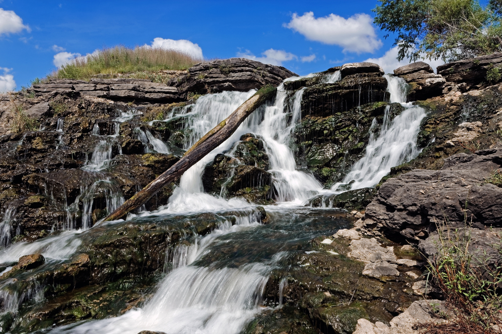 The water rushes over the Lake MacBride Waterfall. This waterfall has several main falls and numerous smaller falls.
