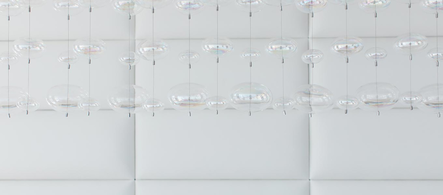 crypton-home-white leather wall and chandelier