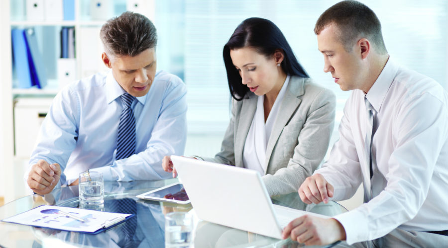 Image of confident partners working with modern communication device at meeting
