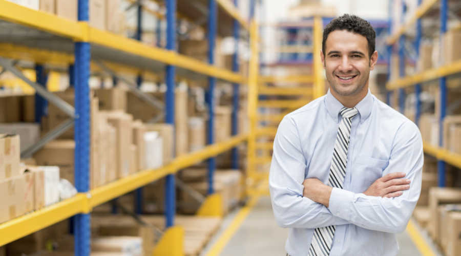 Successful business man working in a warehouse and looking at the camera smiling - trading concepts