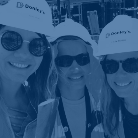 Donley's women smiling wearing hard hats and sunglasses