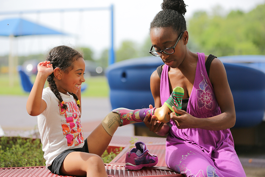 Audrey McFadden on a playground with her mother, Clarissa. Prosthetic. Family.
