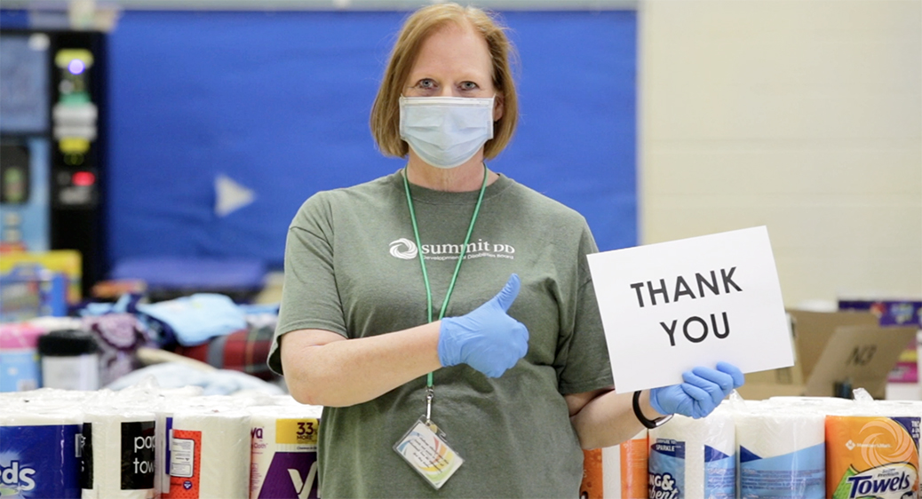 Summit DD staff member wearing a mask and holding a Thank You sign.