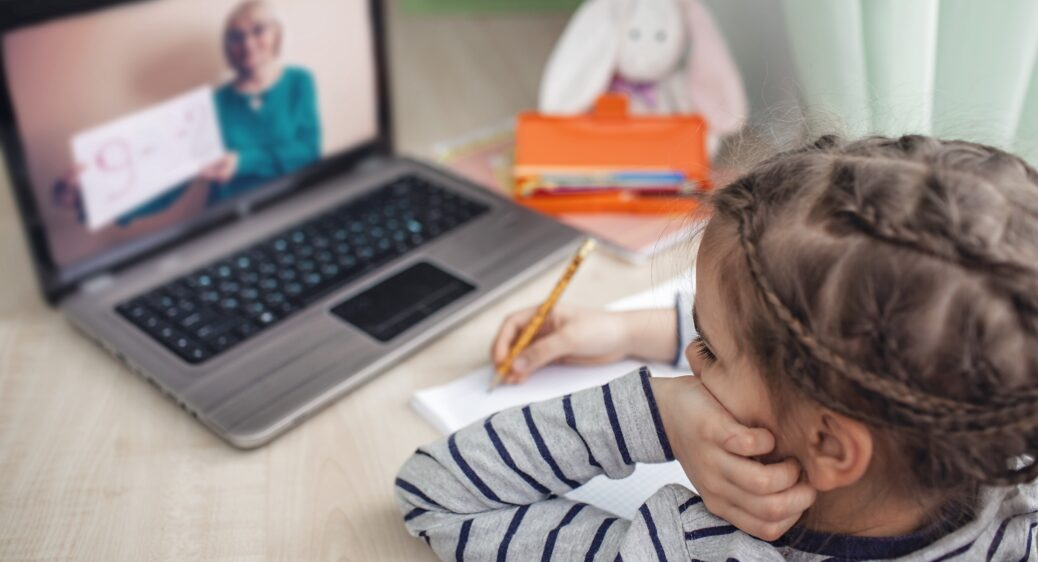 Young girl at computer, learning remotely