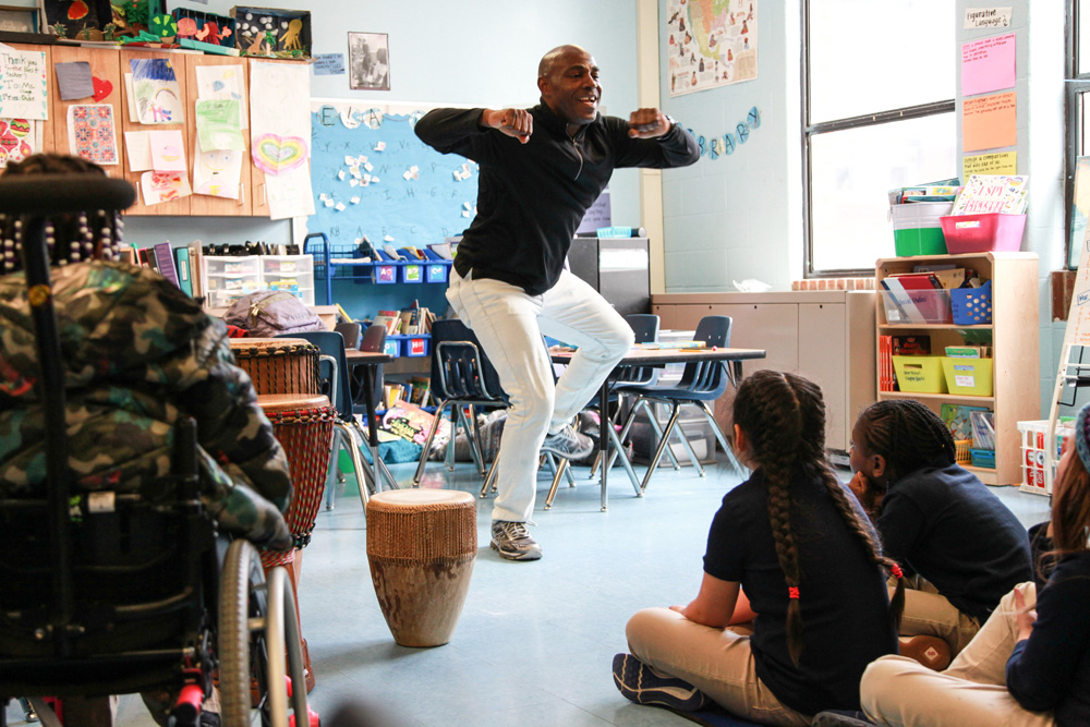 Teaching artist Ssuuna dances as children seated around him watch intently