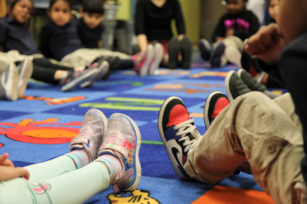 Students and teachers sit in a circle on the floor, feet outstretched. Children imagine their colorful sneakers are transformed into tap shoes and are in position to stomp out beats.