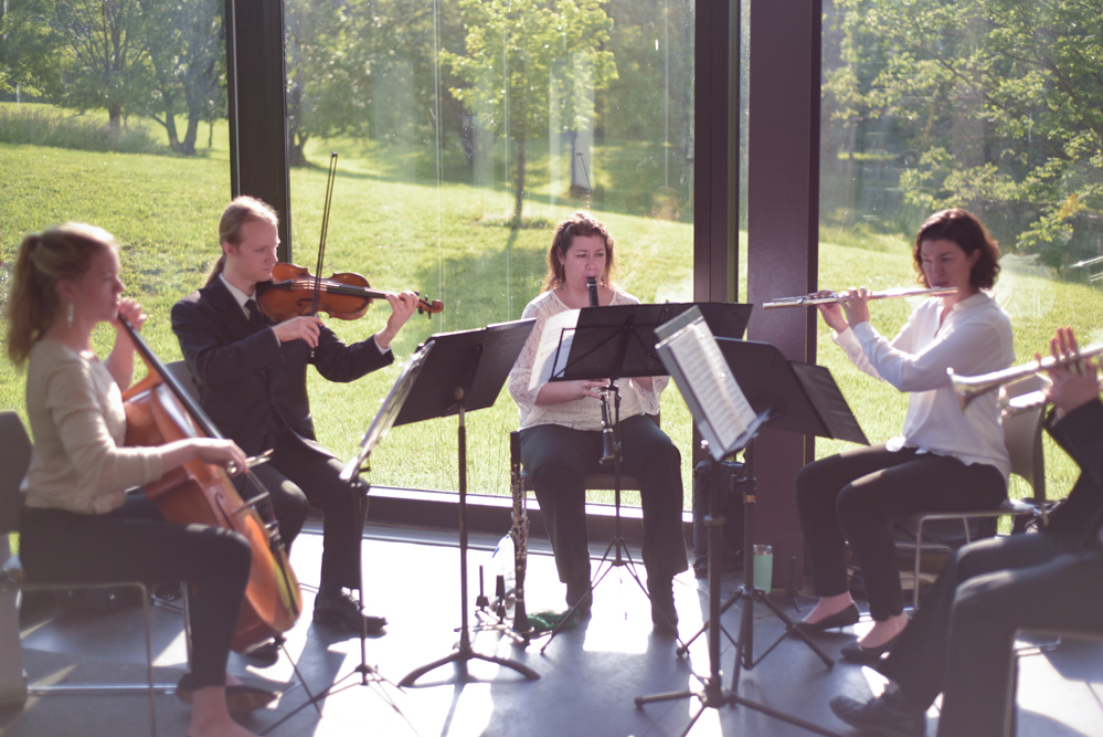 Musicians play stringed and brass instruments in the sunlit atrium.