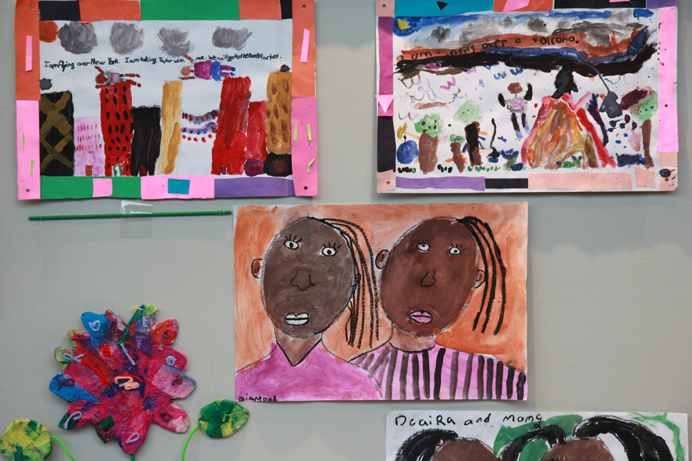 A collection of student artwork: A bright tissue paper flower, a painted portrait of two girls with long eye lashes dressed in pink, and two paintings of figures flying over the high rises of New York City and over a volcano.