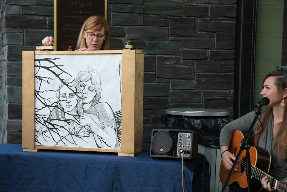 Artist Maura Dwyer turns a large scroll revealing a hand-drawn illustration of woman with her arms enveloping a younger woman's shoulders. Playing guitar beside the artist is folk musician Letitia VanSant.