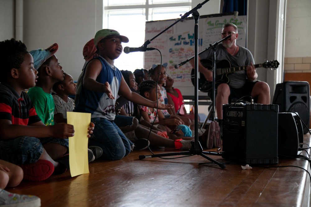 Children kneeling on stage around a microphone and taking turns singing into it with musician Scott Paynter accompanying them on guitar.