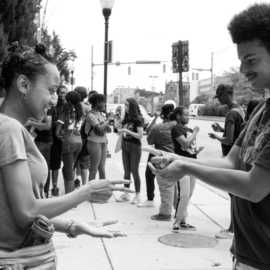 Two high school interns playing Rock, Paper, Scissors on the sidewalk outside of Motor House on North Ave. in Baltimore. A larger group of high school students are gathered in the background.
