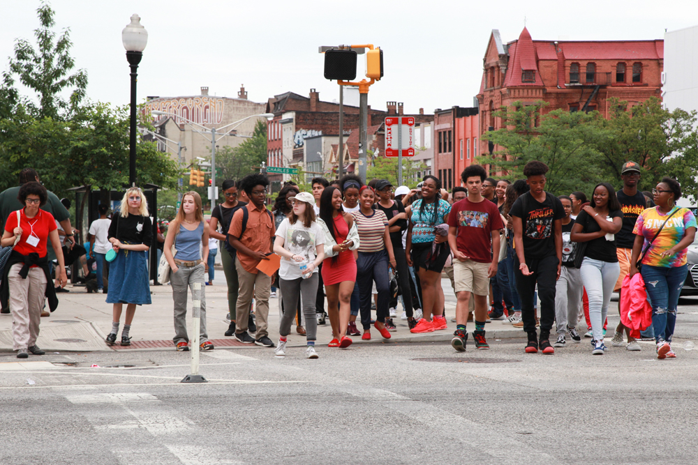 More than 30 high school students in the crosswalk with buildings along North Avenue in the distance behind them.