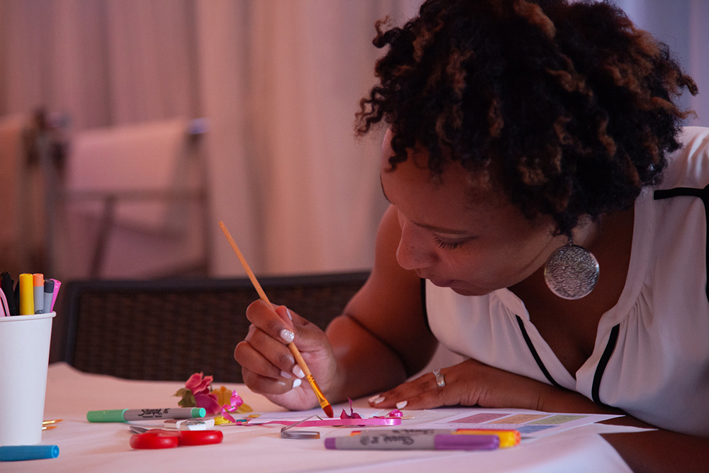 Principal Reese uses watercolor to create her wish banner at the Principal's Fellowship dinner