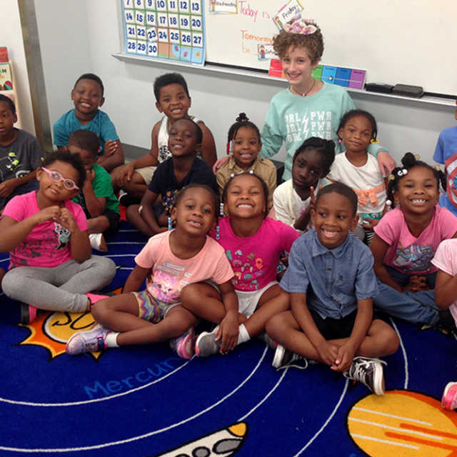 The Pre-K class sitting together on a rug depicting the solar system, posing with Alice, a student volunteer.