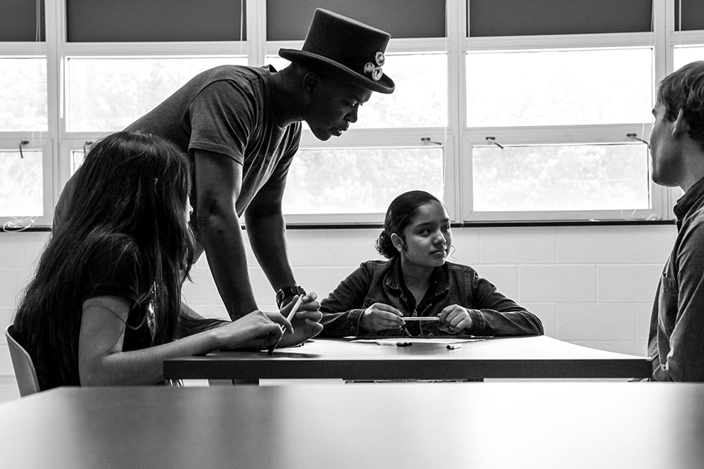 Spoken word artist Femi the Drifish stands at a table where students are seated looking over their work.