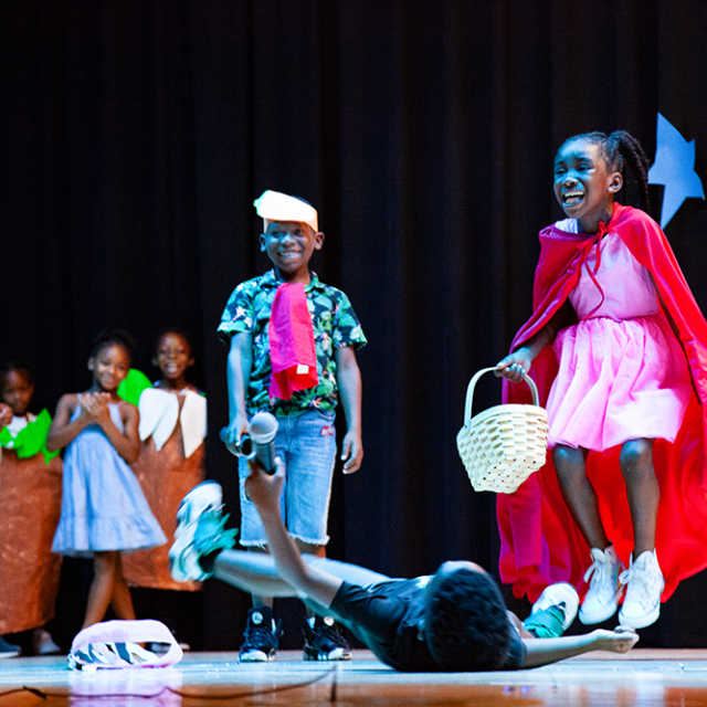 Children performing their own version of Little Red Riding Hood