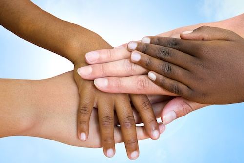 Close up of multi ethnic children's hands making pile against blue sky.