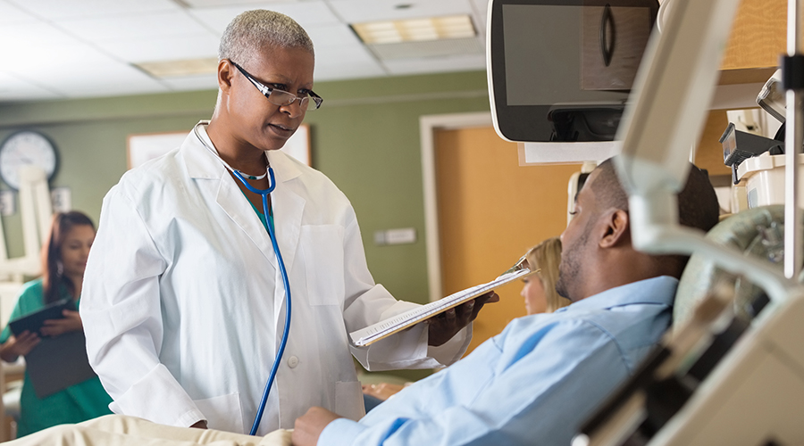 Female African American doctor explaining chart to patient in hospital