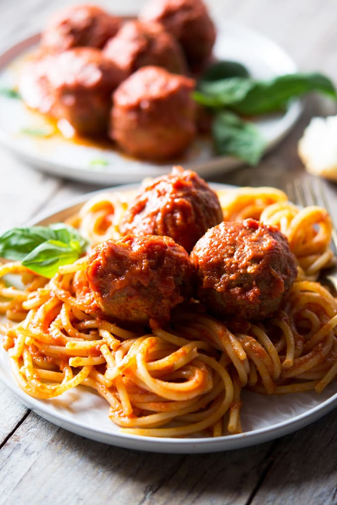 a side shot of mozzarella stuffed meatballs with spaghetti