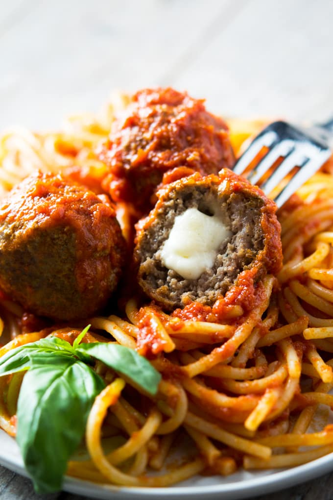 Mozzarella stuffed meatballs cut in half with mozzarella oozing out