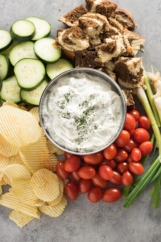 dill dip with vegetables chips and bread