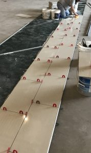 Tiling the main aisles of a furniture showroom requires precise layout to ensure tile rows are aligned on center with columns.