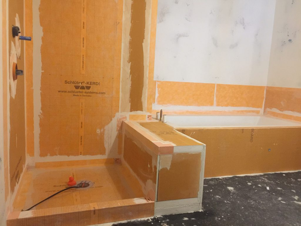 Waterproofing membrane was wrapped from the wall to the tub deck to create a waterproof splash zone for the tub area.