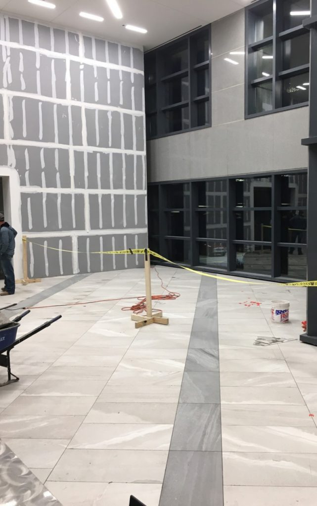 After installing floor tiles, David Allen Company prepped the walls for the large-format gauged panel installation.
