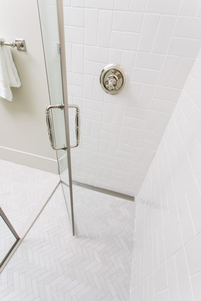 Basketweave white tiles on shower wall, white wood look tiles on floor