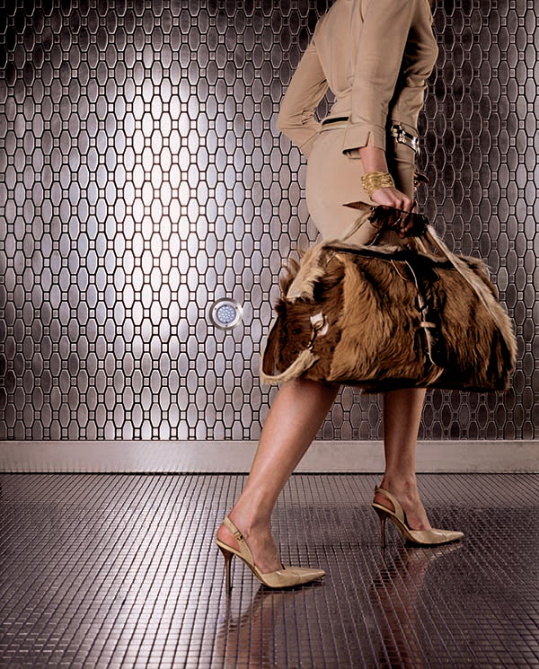 woman in high heels walking on metal mosaic floor with elongated hex metal wall mosaics