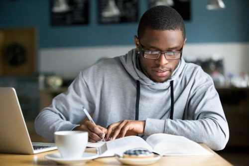 Man wearing glasses studies for GMAT in front of laptop with coffee.