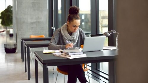 Woman reviews GMAT topics on a laptop in an open co-work space.