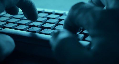 Set of hands typing on keyboard in dark room.