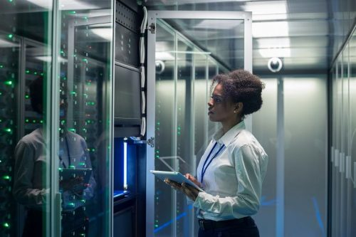 Female network security architect holding an tablet stands in a room full of computers and technology.