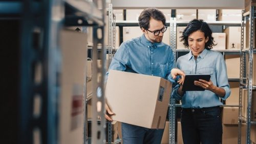 Man holding a box and woman holding a tablet review inventory and data in a storage room.