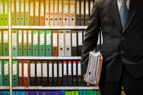 Accountant holds a stack of papers at his side while standing in front a a floor-to-ceiling bookcase full of binders.